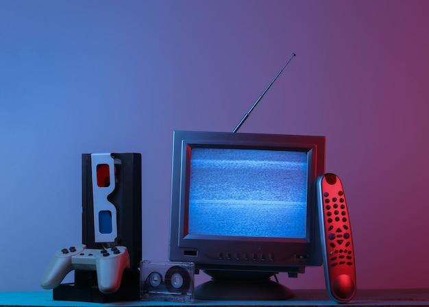 Récepteur de télévision à l'ancienne antenne, lunettes anaglyphes, horloge, cassette audio et vidéo, manette de jeu, télécommande en néon dégradé bleu rose. vague rétro