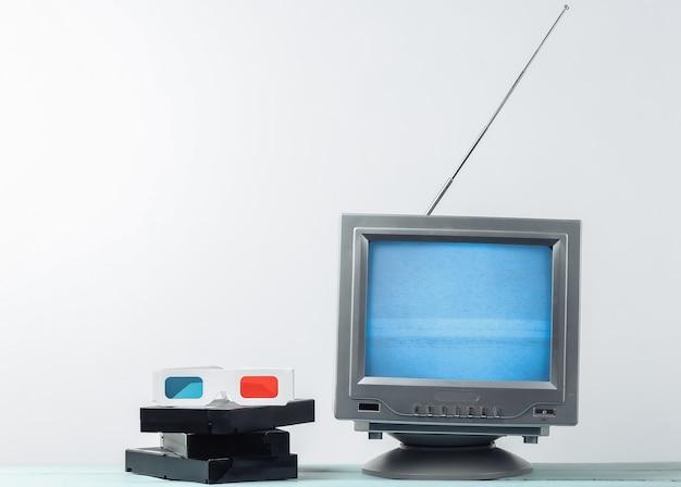 Récepteur de télévision rétro à l'ancienne d'antenne, lunettes 3d anaglyphes et cassettes vidéo sur mur blanc.