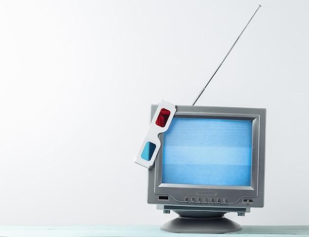 Récepteur de télévision rétro à l'ancienne d'antenne avec des lunettes stéréo anaglyphes sur un mur blanc.