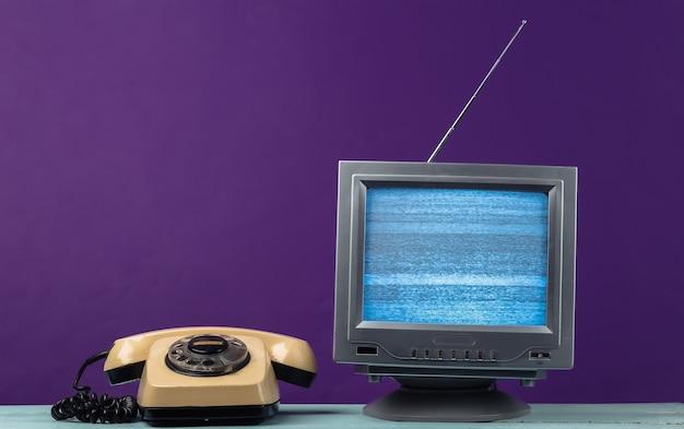 Récepteur de télévision rétro à l'ancienne d'antenne et téléphone rotatif sur violet