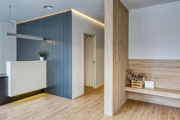 Réception au design moderne avec bureau, fleurs, murs blancs et grilles grises. parquet et écran en bois. couloir avec portes blanches clinique dentaire