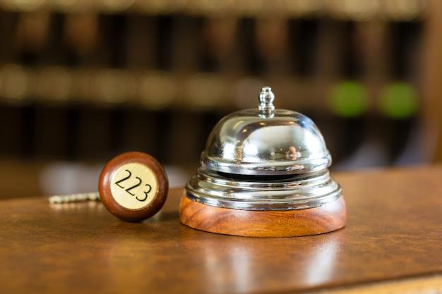 Réception, cloche de l'hôtel et clé posée sur le bureau