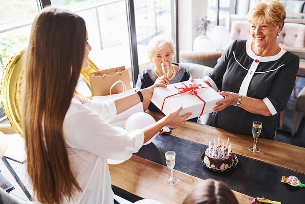 Réception du coffret cadeau. femme âgée avec famille et amis célébrant un anniversaire à l'intérieur.
