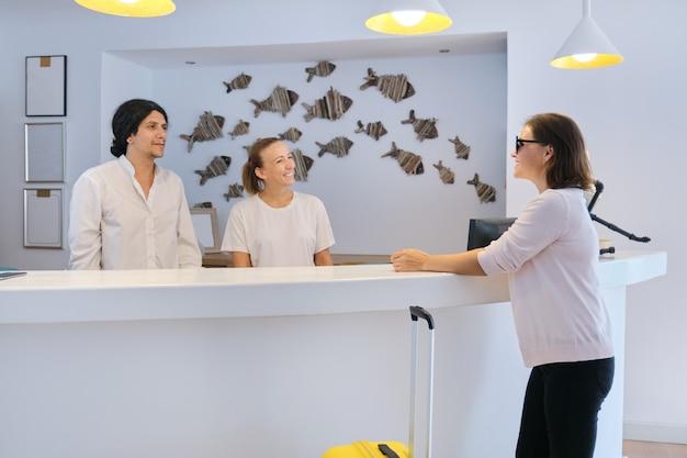 Réception à l'hôtel de villégiature. réceptionnistes homme et femme sur le lieu de travail. enregistrement des clients à la réception