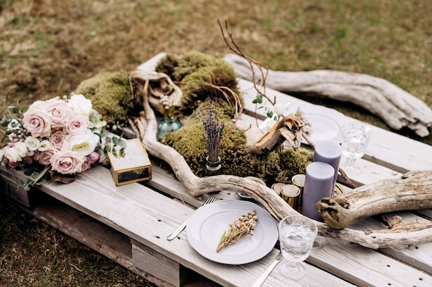 Réception de table de dîner de mariage une table impromptue pour deux de la palette de construction sur l'herbe grise