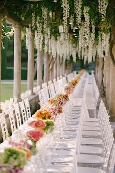 Réception de table de dîner de mariage une très longue table pour les invités avec une nappe blanche fleurie