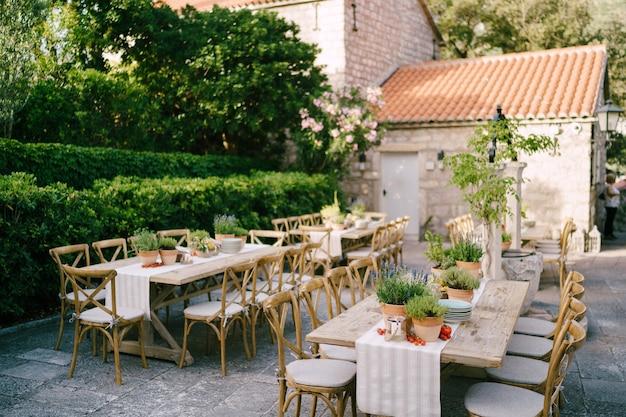 Réception de table spéciale au coucher du soleil à l'extérieur d'anciennes tables en bois rectangulaires avec chemin de chiffon
