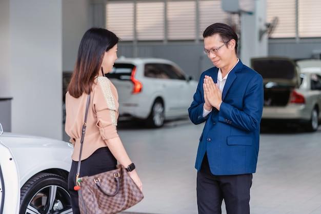 Réceptionniste asiatique accueillant le client pour visiter le centre de service de maintenance pour vérifier la voiture dans la salle d'exposition