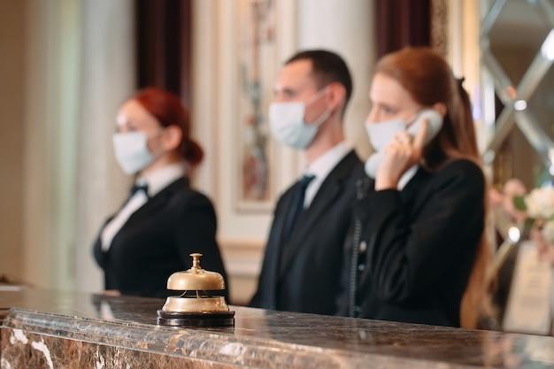 Réceptionniste au comptoir de l'hôtel portant des masques médicaux