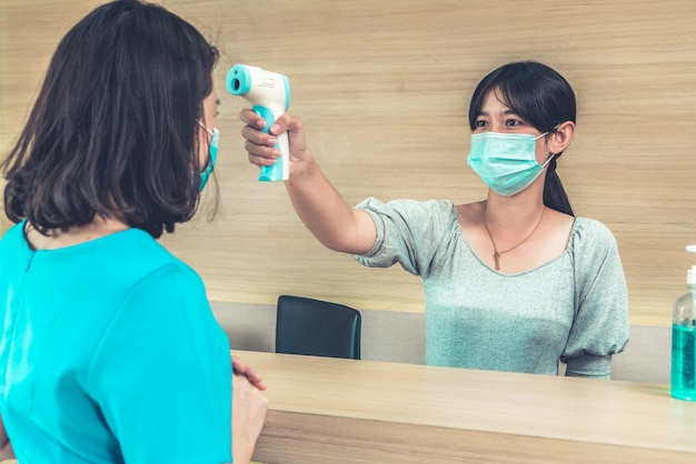 Réceptionniste et invité portant un masque facial à la réception.