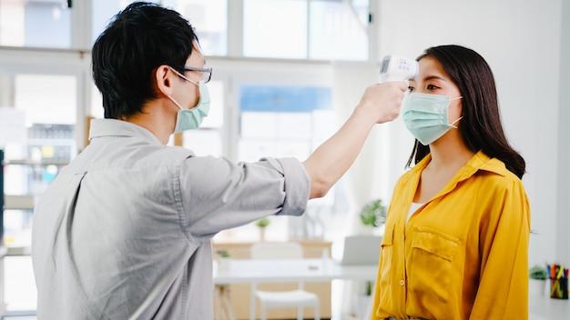 La réceptionniste masculine d'asie portant un masque protecteur utilise un thermomètre infrarouge ou un pistolet thermique sur le front du client avant d'entrer dans le bureau. mode de vie nouveau normal après le virus corona.