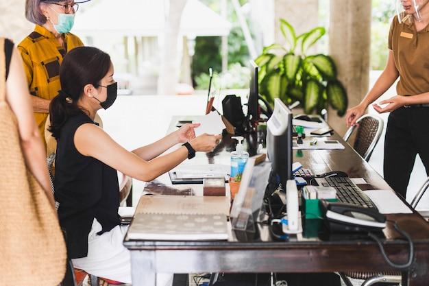 Réceptionniste de mise au point sélectionnée avec écran facial donnant une enveloppe aux clients de l'hôtel.