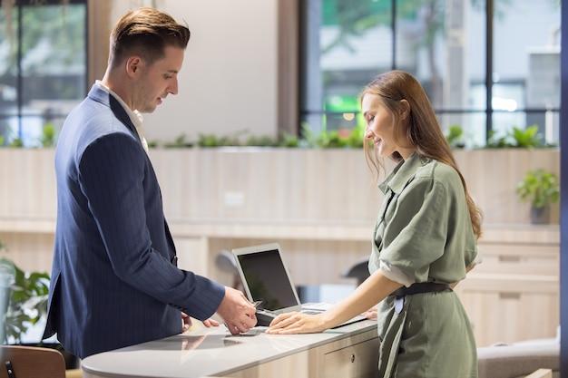 Réceptionniste prenant le paiement par carte de crédit, chargez-le sur mon compte courant au comptoir de l'hôtel