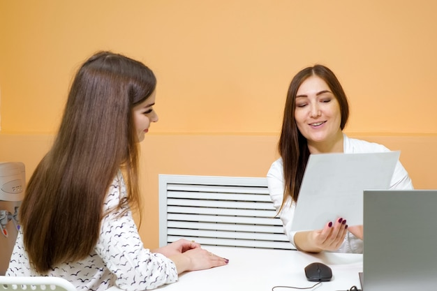 Une réceptionniste professionnelle tient une feuille de papier et parle à un visiteur aux cheveux longs dans un salon de beauté moderne