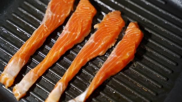 Recette de cuisson du poisson morceau de filet de saumon ou de truite frit sur une poêle grillée