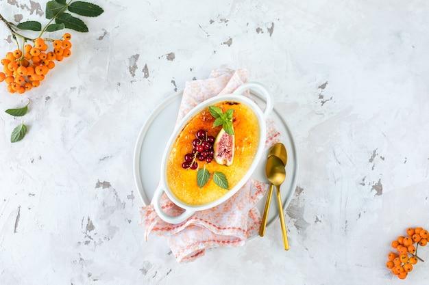 Recette de dessert crème brûlée aux figues fraîches et groseilles sur une assiette blanche dans une composition d'automne, espace de copie. vue de dessus