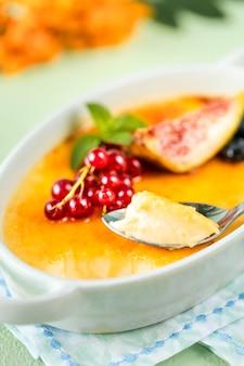 Recette de dessert crème brûlée aux figues fraîches, myrtilles et groseilles sur une table en pierre verte en composition d'automne.