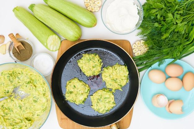 Recette étape par étape pour cuire des crêpes de courgettes et de légumes verts sur fond clair. avec l'ajout d'oeufs, farine, ail, poivre. la vue d'en haut