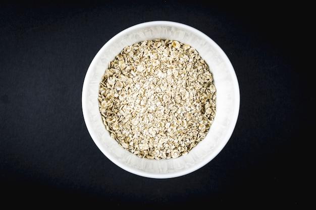 Recette de flocons d'avoine aux noix, pruneaux, cannelle et sucre. flocons d'avoine dans une tasse blanche