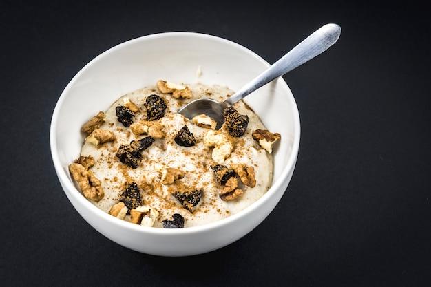 Recette de flocons d'avoine avec noix, prunes, cannelle et sucre préparé pour le petit déjeuner avec une cuillère sur fond noir