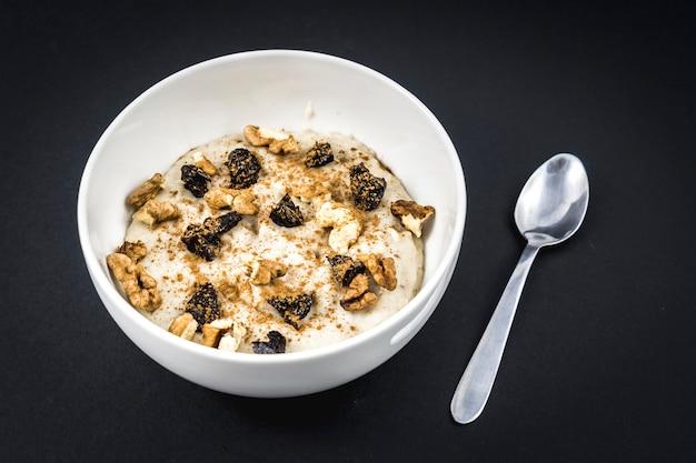 Recette de flocons d'avoine avec noix, prunes, cannelle et sucre préparé pour le petit déjeuner sur fond noir