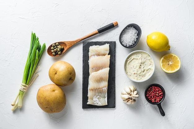 Recette d'ingrédients traditionnels de poisson et frites filets de morue crus sur ardoise en pierre