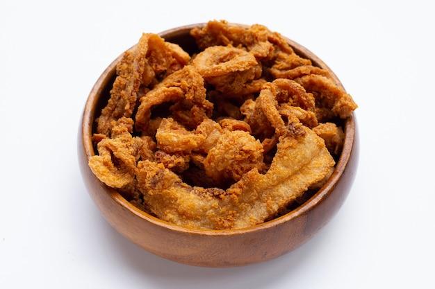 Recette de poitrine de porc croustillante frite dans un bol en bois sur fond blanc.