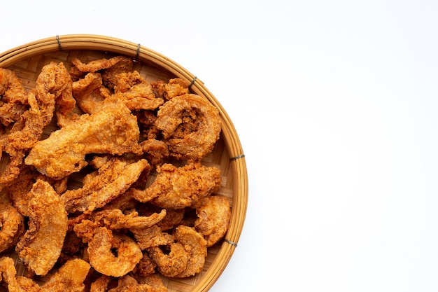 Recette de poitrine de porc croustillante frite dans un panier en bambou sur fond blanc.