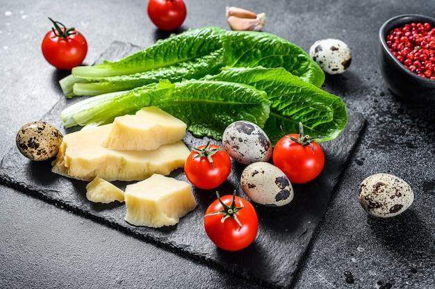 Recette de salade césar, laitue romaine, tomates, œufs, parmesan, ail, poivre. fond noir. vue de dessus.