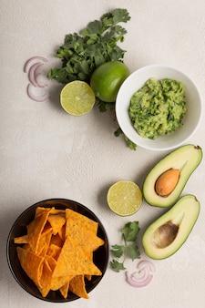 Recette de sauce mexicaine au guacamole, ingrédients sur une table de cuisine blanche, vue du dessus