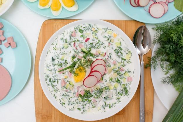 Recette de soupe okroshka froide nationale russe dans une assiette blanche sur une lumière