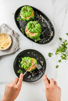 Recettes d'automne. femme mange du poivron farci fait maison avec de la viande hachée, des carottes, des tomates, des herbes, du fromage. sur une table en marbre blanc, dans une assiette portionnée, les mains dans l'image, copie espace vue de dessus