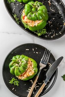 Recettes d'automne. poivron farci maison avec viande hachée, carottes, tomates, fines herbes, fromage. , en assiette portionnée, avec couteau et fourchette, vue de dessus