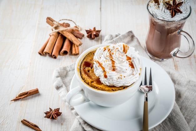 Recettes avec citrouilles, restauration rapide, repas micro-ondes. tarte épicée à la citrouille dans une tasse, avec crème fouettée, crème glacée, cannelle, anis. sur une table en bois blanc, avec une tasse de chocolat chaud. fond