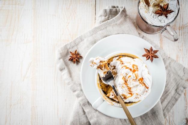 Recettes avec citrouilles, restauration rapide, repas micro-ondes. tarte épicée à la citrouille dans une tasse, avec crème fouettée, crème glacée, cannelle, anis. sur une table en bois blanc, avec une tasse de chocolat chaud. vue de dessus du fond
