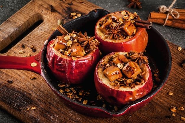Recettes de cuisine d'automne. pommes au four farcies de muesli, caramel et épices. sur table en pierre noire, dans une poêle, copyspace