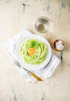 Recettes de cuisine vegan à la mode, pâtes spaghetti au fromage et courgettes avec jaune d'oeuf au parmesan, huile d'olive et feuilles de basilic, surface en béton léger