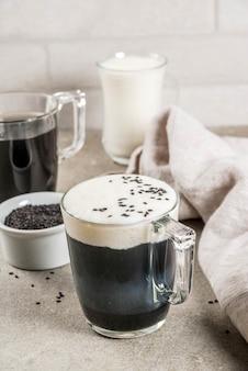Recettes végétaliennes à la mode, cappuccino de sésame noir avec graines de sésame et lait de coco fouetté, table en pierre grise, fond