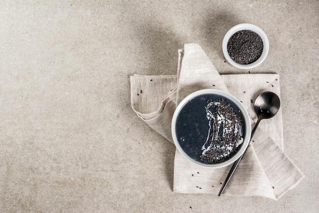 Recettes végétaliennes à la mode, soupe de sésame noir aux graines de sésame et lait de coco, table en pierre grise, vue de dessus du fond
