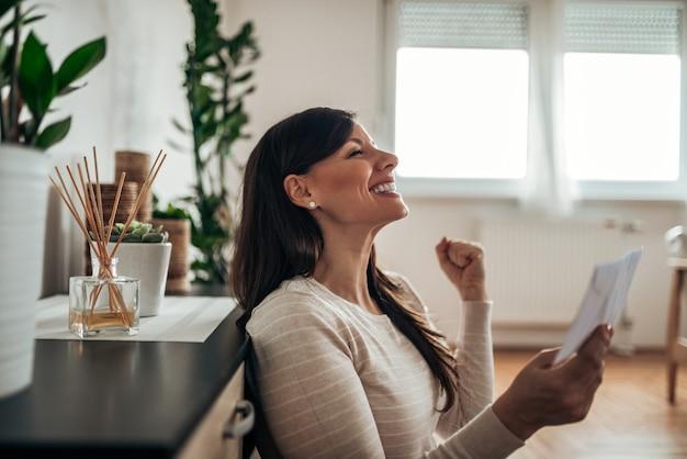Recevoir une lettre avec de bonnes nouvelles. femme excitée heureuse de bonnes nouvelles.