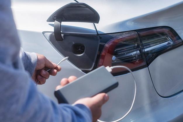 Recharge de véhicule électrique. l'homme tient une banque d'alimentation avec un câble dans les mains dans le contexte d'une voiture électrique.