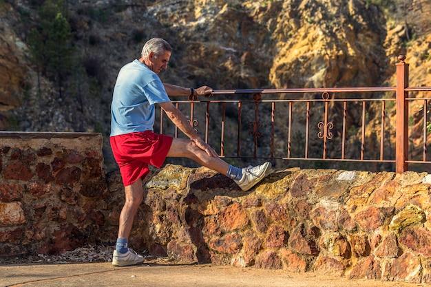 Réchauffez-vous d'abord. homme concentré debout sur la campagne et s'étendant la jambe