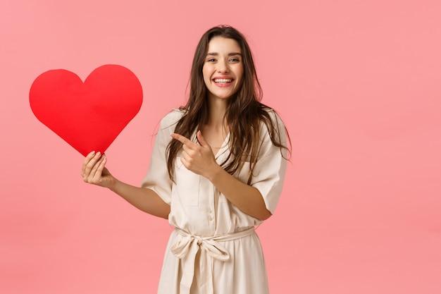 Recherche d'âme soeur. joyeuse jolie fille souriante en robe, tenant un gros coeur rouge, pointant le carton de la saint-valentin et regardant, veut montrer de l'affection et de l'amour, mur rose