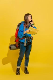 Recherche de chemin avec la carte. portrait d'une joyeuse jeune fille touristique caucasienne avec sac et jumelles isolé sur fond jaune studio. se préparer au voyage. resort, émotions humaines, vacances.