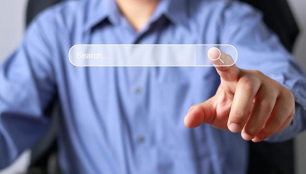 Recherche de concept de réseautage d'informations sur les données internet, technologie de recherche de données, optimisation des moteurs de recherche, main masculine appuyant sur le bouton de recherche.
