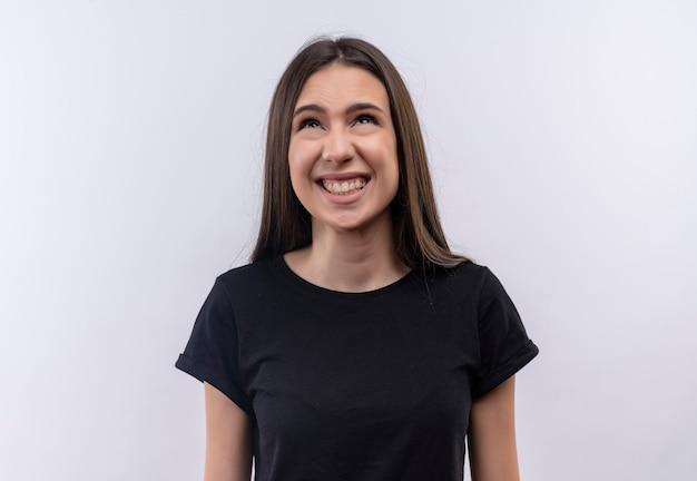 À la recherche de confus jeune fille caucasienne portant un t-shirt noir sur un mur blanc isolé