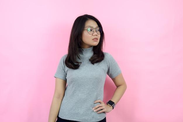 À la recherche d'un côté avec un visage sérieux belle femme indonésienne asiatique portant un col roulé gris