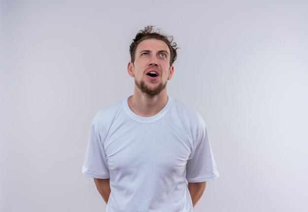 À la recherche de désolé jeune homme portant un t-shirt blanc, tenant les mains sur le dos sur fond blanc isolé