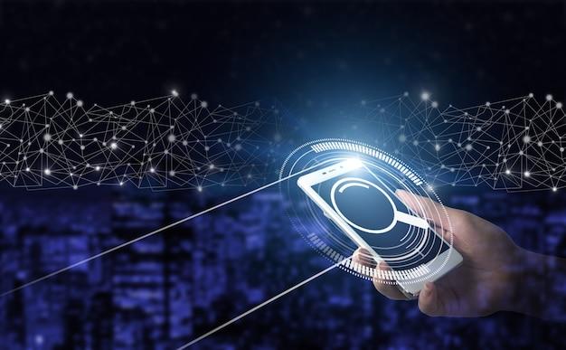 Recherche de données internet. concept de navigation web. tenir à la main un smartphone blanc avec un signe de données de recherche d'hologramme numérique sur le dos flou sombre de la ville. recherche de données d'information sur les réseaux internet.