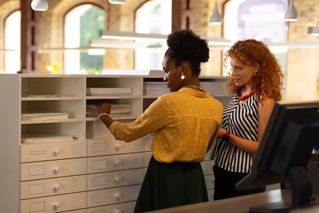 Recherche dossier. deux beaux travailleurs élégants debout près du tiroir et à la recherche d'un dossier